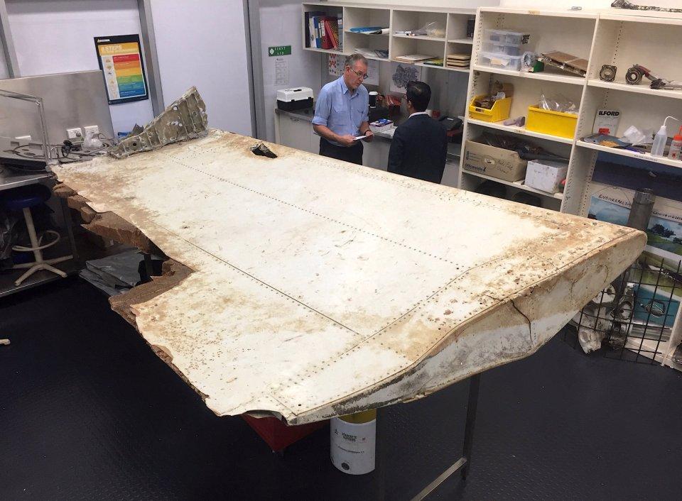 Australian and Malaysian officials examine aircraft debris at the Australian Transport Safety Bureau headquarters